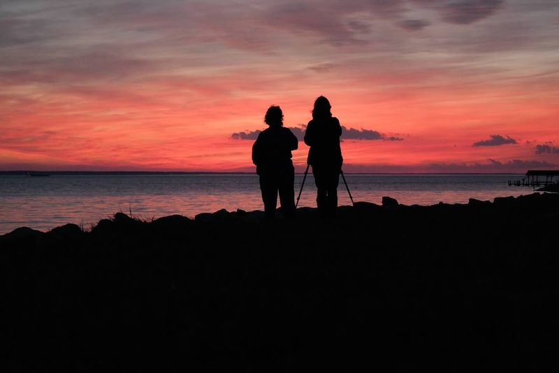 Silhouette of people standing on beach at sunset