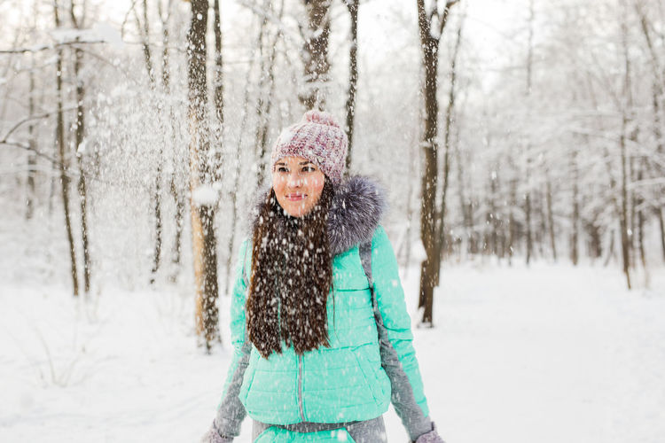 Portrait of smiling woman in snow covered forest