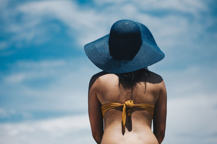 Rear View Of Woman In Bikini Wearing Hat While Standing Against Sky During Sunny Day