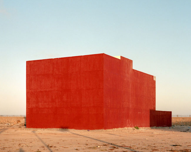 Red brick wall by sea against clear sky