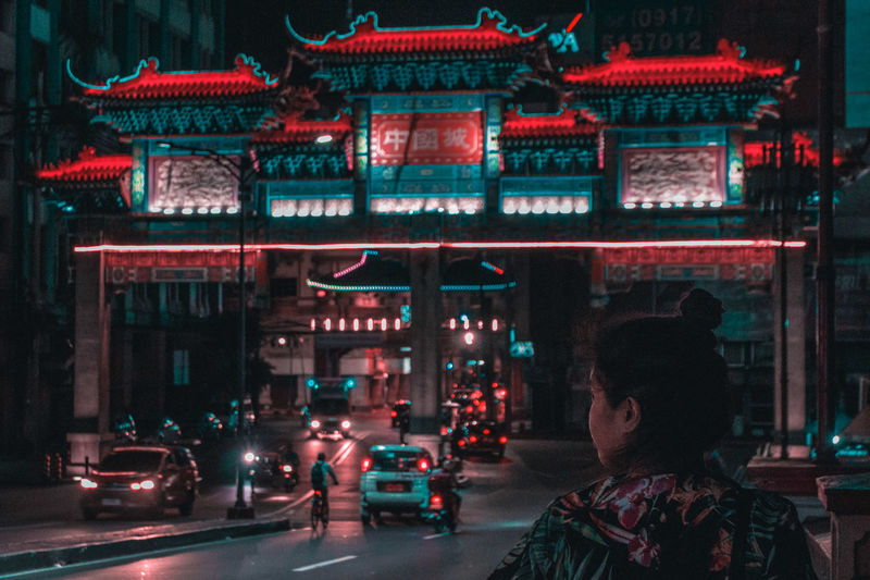 Rear view of young woman standing on illuminated street at night