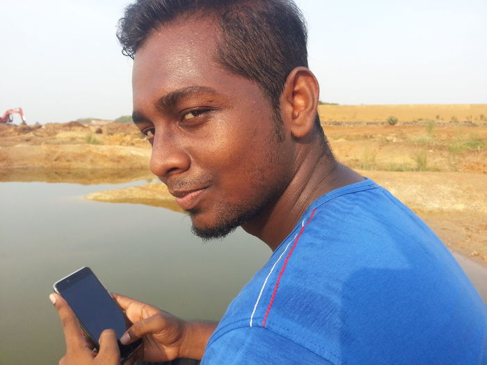 Portrait of young man using smart phone at lake
