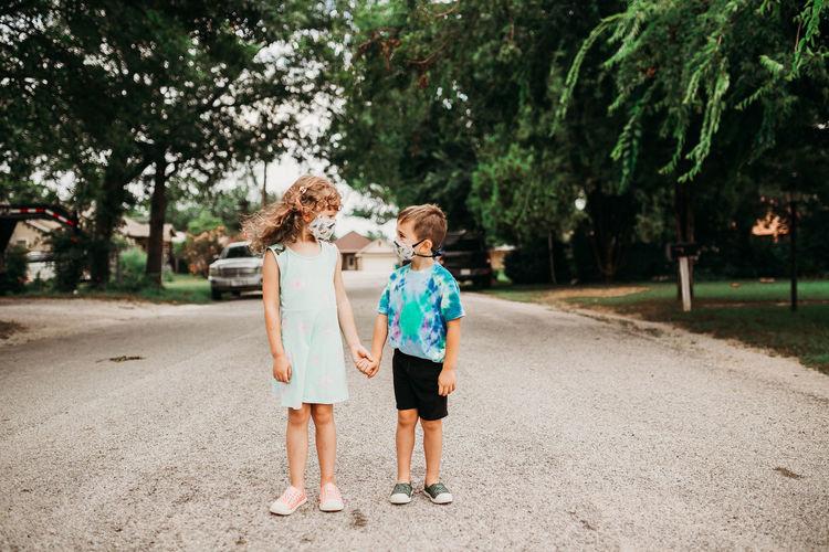 Siblings standing on road amidst trees