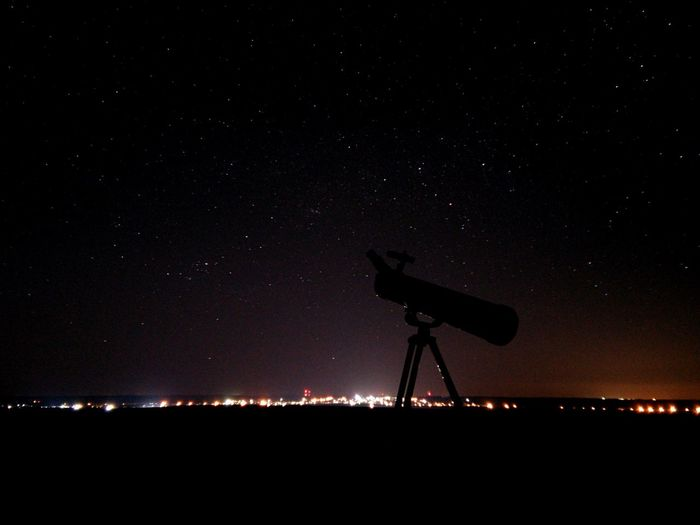 Silhouette telescope against sky at night