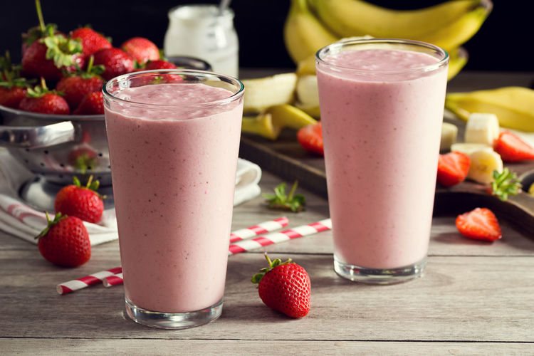 Two Strawberry Banana Yogurt Smoothies or Shakes with Straws and Ingredients on Wooden Table Banana Berries Drinks Food And Drink Ingredients Pink Smoothies Blended Drink Cold Drink Food Frappe Fruit Glass Healthy Making Nobody Shake Smoothie Straw Strawberry Strawberry Banana Smoothies Table Two Yogurt