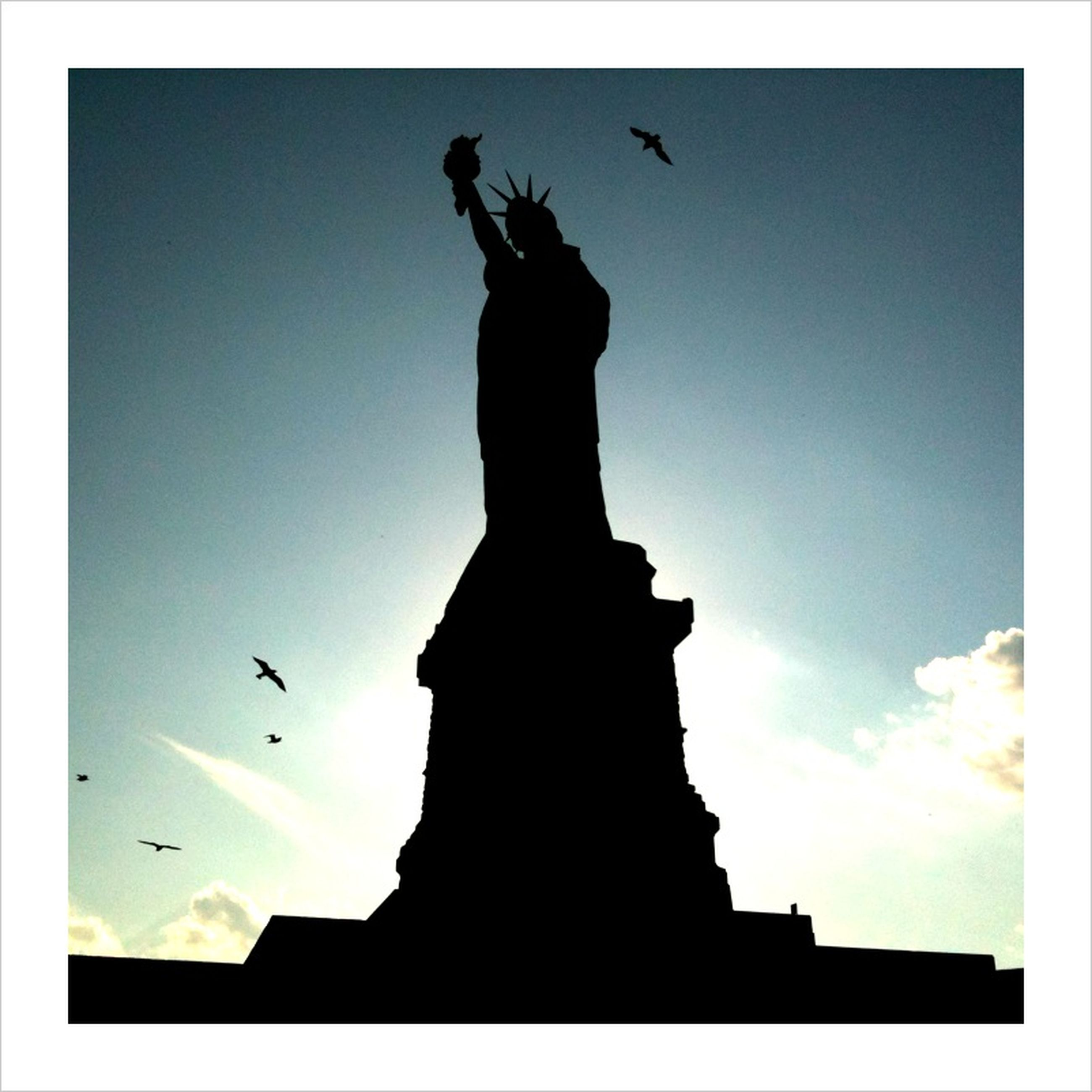 low angle view, silhouette, bird, flying, statue, sky, transfer print, sculpture, animal themes, animals in the wild, wildlife, human representation, mid-air, auto post production filter, clear sky, spread wings, art and craft, sunset, built structure