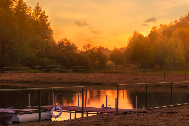Pond Beauty In Nature Cloud - Sky Golden Hour Lake Landscape Mode Of Transportation Nature Nautical Vessel No People Non-urban Scene Orange Color Outdoors Plant Reflection Scenics - Nature Sky Summer Evening Sunset Tranquil Scene Tranquility Transportation Tree Water
