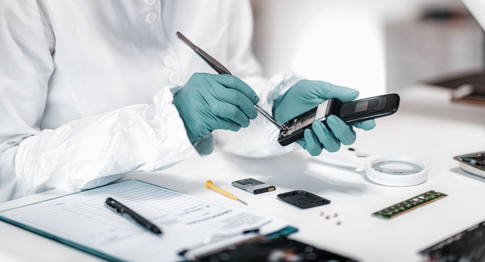 Midsection of detective repairing mobile phone on table