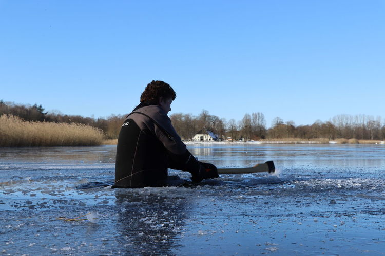 Man sitting on frozen lake against clear sky during winter