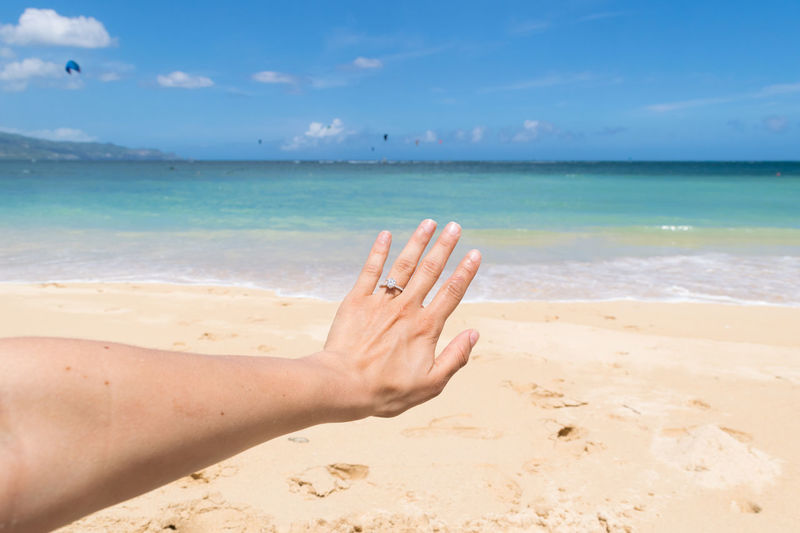 Close-up of hand at beach against sky