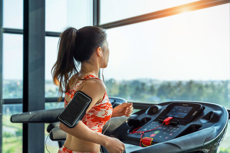 Young woman exercise with exercise-machine in gym. One Person Real People Women Lifestyles Transportation Mode Of Transportation Adult Day Window Hairstyle Sunlight Car Focus On Foreground Outdoors Brown Hair Young Adult Motor Vehicle Side View Beautiful Woman
