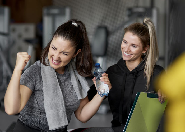Smiling instructor looking at excited woman in gym