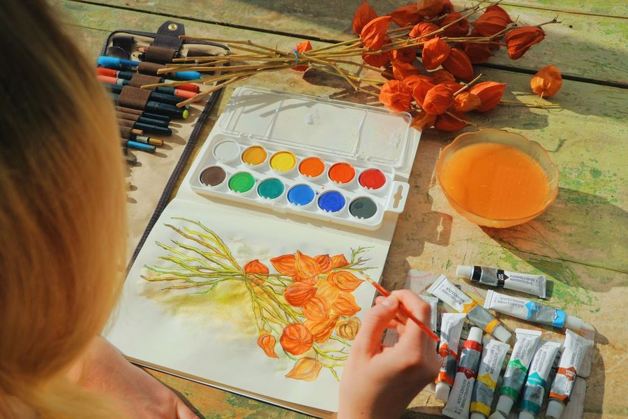 female artist/painter painting a watercolour picture of a physalis plant into her notebook Indoors  Overhead Abstract Art Artist ArtWork Brush Cozy Creative Creativity DIY Drawing Flower Handmade Illustration Illustrator Painter Painting Student Studio Sunlight Table Vibrant Color Watercolour Woman
