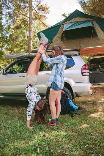 Woman Helping Friend In Doing Handstand By Car At Forest