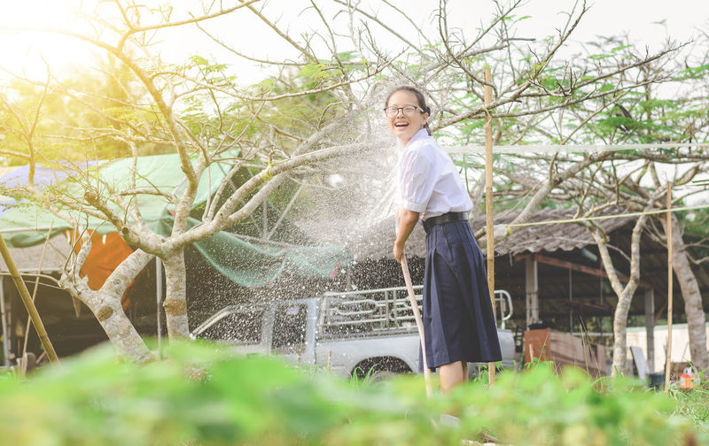 Water spraying on cheerful woman standing at park