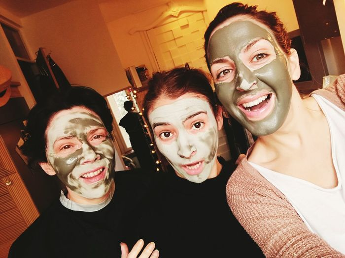 Portrait of playful female friends with facial masks on their face while at home