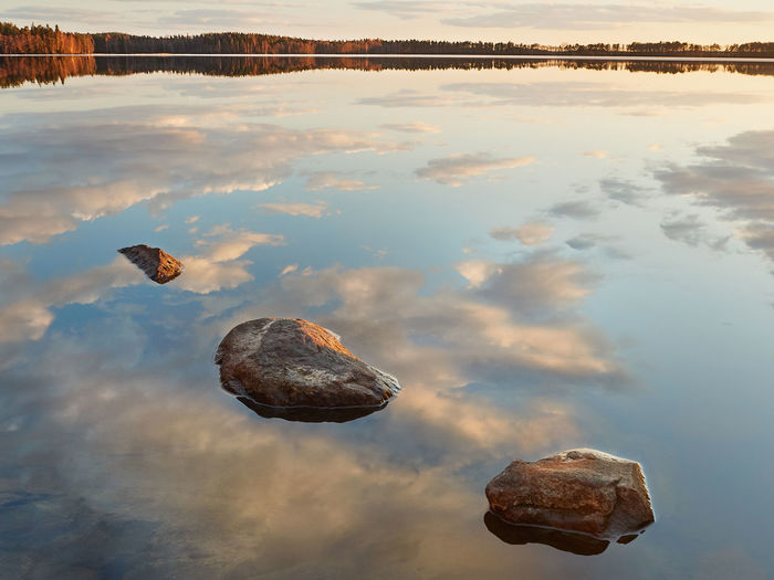 Rocks in the still water of a lake in summer. Beauty In Nature Blue Calm Calm Water Cloud - Sky Lake Majestic Nature No People Non-urban Scene Outdoors Peaceful Reflection Rocky Coastline Scenic View Scenics Standing Water Still Summer Sunset Tranquil Scene Tranquility Water Waterfront