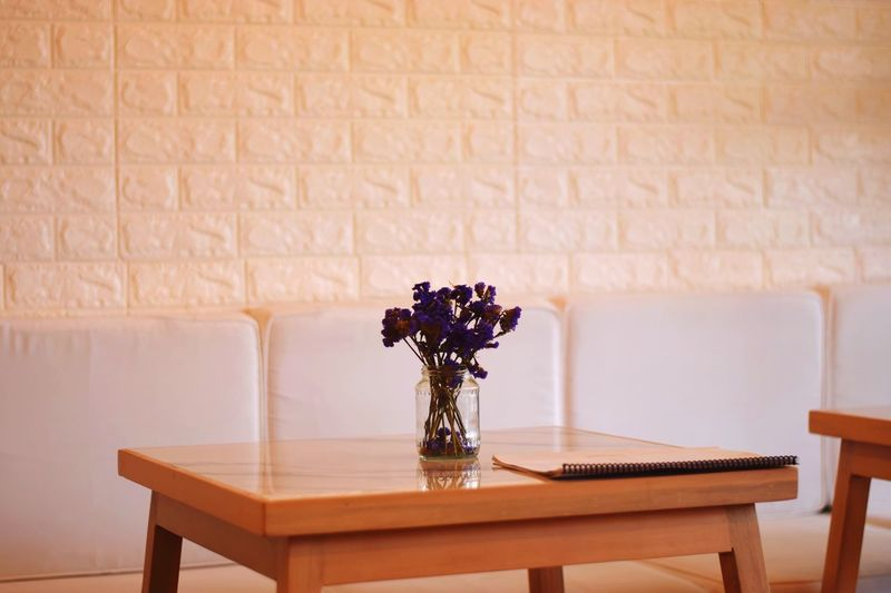 Flowers in vase on table against wall at home