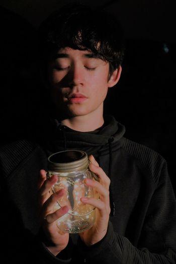 Man Holding Illuminated String Lights In Jar