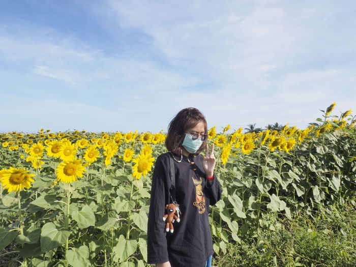 Young woman standing in sunflower field