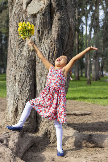 Full length of girl with arms raised standing in park