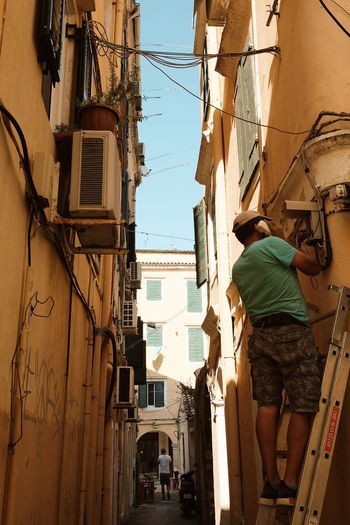 Eye4photography  EyeEm Selects EyeEm Gallery Sunlight Sun Sunlight And Shadow Light And Shadow People Watching People Summer Hot Day Holiday Vacation Greece Streetphotography Street Urban City Residential Building Sky Architecture Building Exterior Built Structure Power Line  Power Supply Alley Building Historic Electricity  Residential Structure