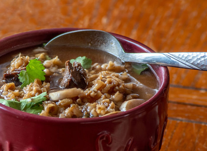 Savory beef and barley soup with mushrooms and a touch of fresh cilantro in a mug