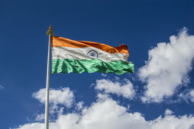 Low angle view of indian flag against blue sky during sunny day