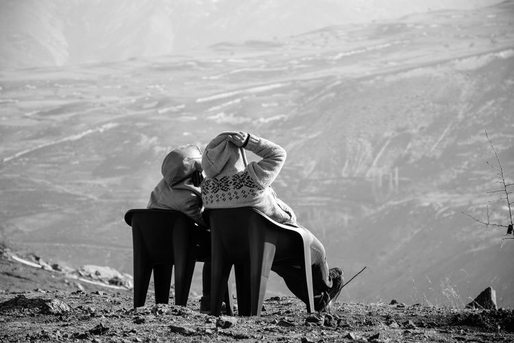 Rear view of couple sitting on land