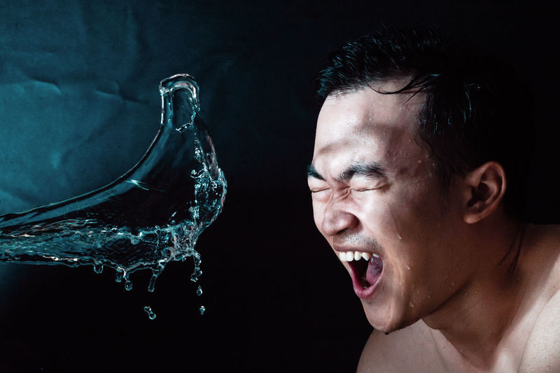 Close-up of shirtless man making face by water against black background