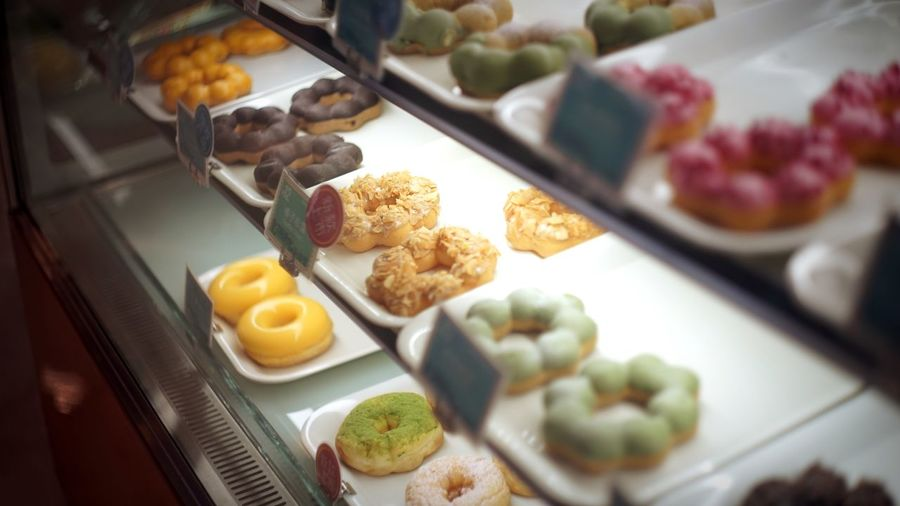Donuts in display cabinet at store for sale