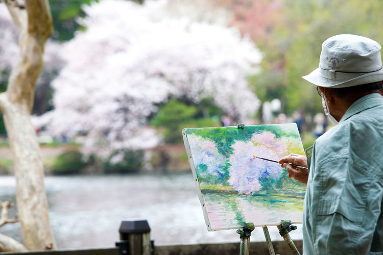 Paintbrush Brush One Person Hat Painter - Artist Palette Creativity Adult Day Artist Nature Leisure Activity Holding Easel Artist's Canvas Art And Craft Standing Waist Up Rear View Outdoors