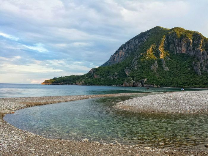 Scenic View Of Cirali Olympos Beach Against Cloudy Sky