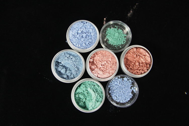Directly above shot of multi colored face powder in containers against black background