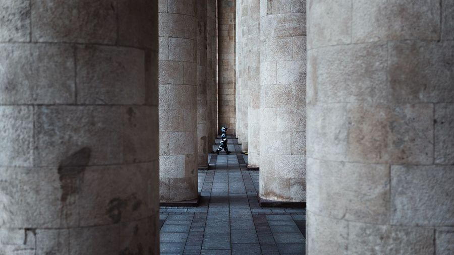 Boy Walking Amidst Columns At Monument