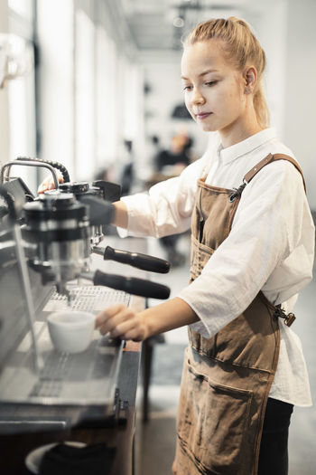 Midsection of woman working in kitchen