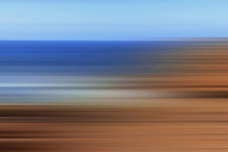 Defocused image of blue sea against sky