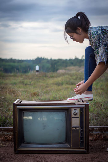 Woman wearing shoe on old television set at farm