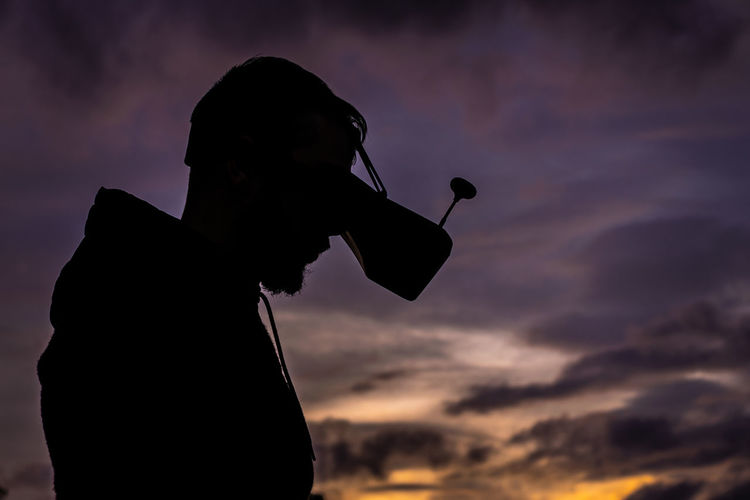 Silhouette man wearing vr goggles against sky