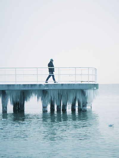Man walkin on iced pier  over water in foggy day
