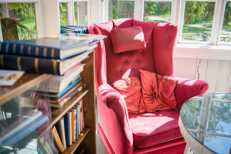High angle view of red armchair by books rack against window