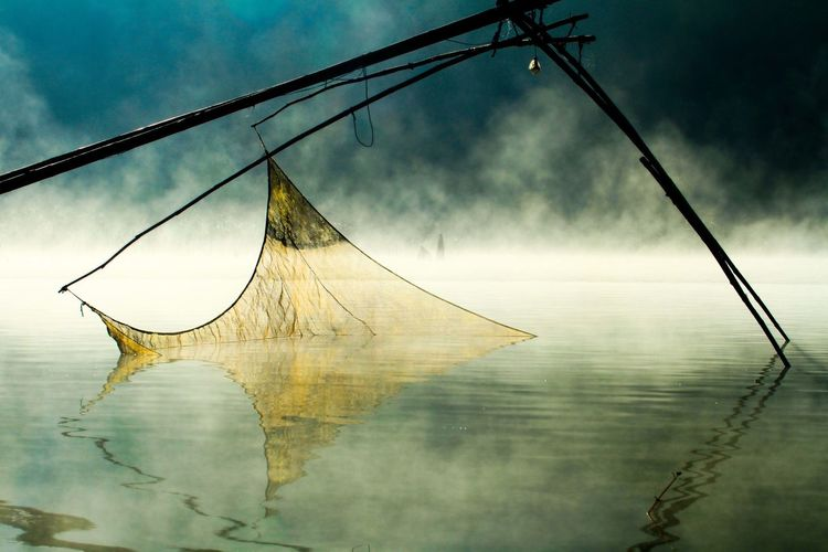 Fishing net on lake during foggy weather