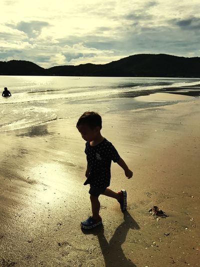 Full Length Side View Of Boy Walking On Shore At Beach