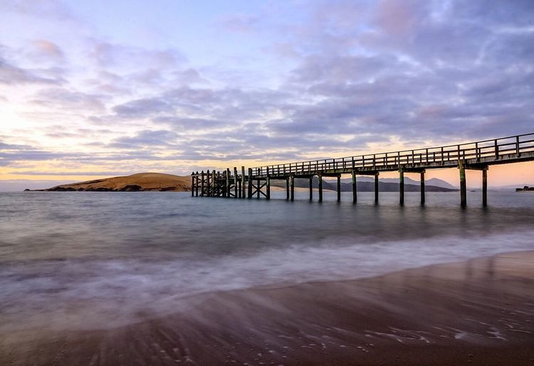 Sea Beauty In Nature Water Cloud - Sky Nature Sky Beach Sunset Wave Outdoors Coastline No People Tranquil Scene Horizon Over Water Scenics Day Pier New Zealand New Zealand Scenery Omapere