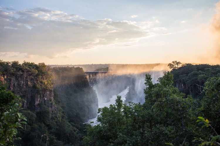 Sunset at victoria falls zimbabwe with the sun cutting through the mist.