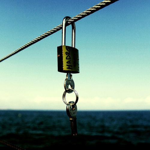 Close-up of key in padlock hanging on metal rope