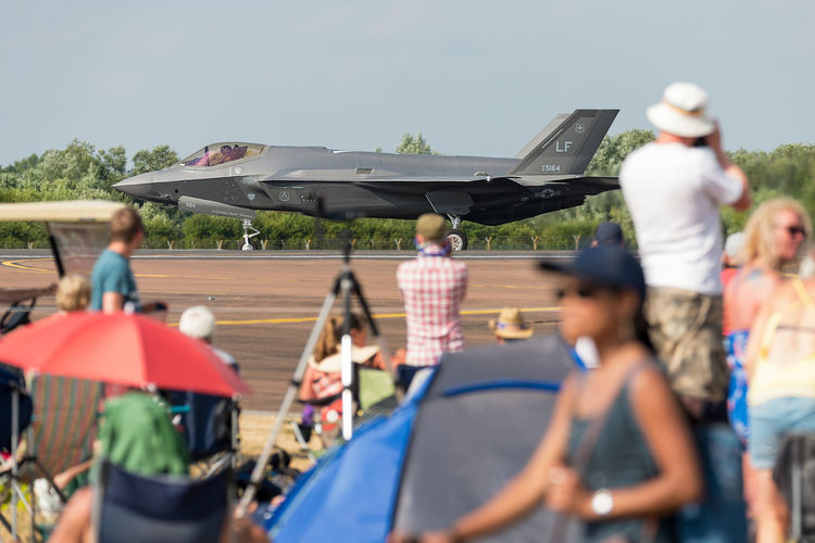 A Lockheed Martin F-35 Lightning II taxiing on the runway at RIAT Fairford 2018, UK, with spectators looking on. F35 Lighting Fairford Air Show Air Vehicle Crowd Day Fighter Jet Group Group Of People Incidental People Leisure Activity Lifestyles Lockheed Martin Men Mode Of Transportation Motion Nature Outdoors People Real People Taxiing Transportation Women