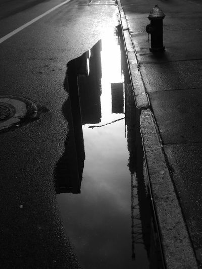 Reflection of buildings in puddle on wet street