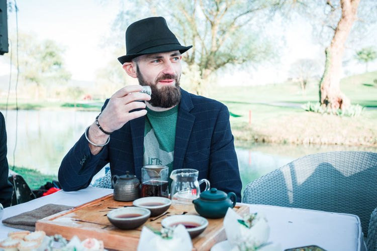 Man looking away while holding tea cup on table