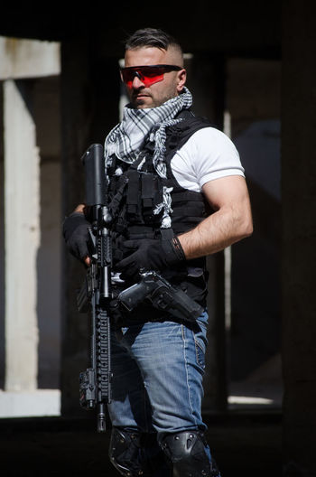 Man holding rifle while standing in building